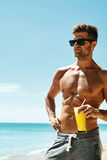 Summer. Athletic Muscular Man Drinking Juice Cocktail On Beach Royalty Free Stock Photos