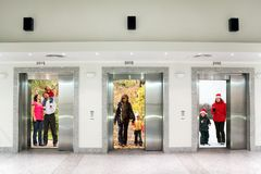 Summer autumn winter family in elevator doors stock photos