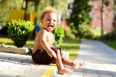 Summer baby boy laugh. Cute little biracial baby boy sittinh on paving and laughing out loud Royalty Free Stock Image