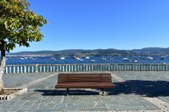 Bench, tree and stone handrail in a beach promenade. Summer background. Bay with blue water, boats and trees. Galicia, Spain. Summer background. Bench and tree stock photography