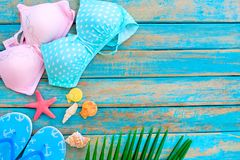 Summer background with bikinis, slippers, starfish, shells and coconut leaves on blue wooden background. Stock Photo