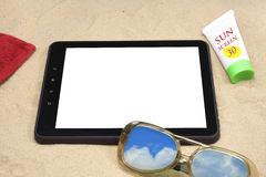 Summer background with digital tablet on the sand. Royalty Free Stock Photography