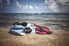 Summer background with flipflops and sunglasses on beach Stock Photos