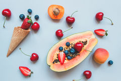Summer background. Fresh juicy berries, papaya and sweet waffle cone on the blue background, top view Royalty Free Stock Image