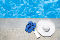 Summer background with hat, flip flops and sunscreen near the po stock photography