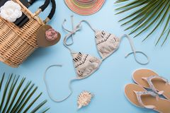 Summer background with palm leaves, fashion hat, bikini, flip flops, straw beach bag on a light pastel blue background, travel and stock photos