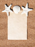 Summer background with paper andseashells on the sand Stock Photography
