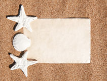 Summer background with paper andseashells on the sand Royalty Free Stock Image