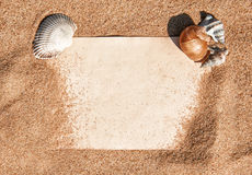 Summer background with paper and seashells on the sand Royalty Free Stock Photos