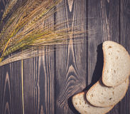 Summer background for postcards in a rustic style. Bread and wheat ears Stock Photos