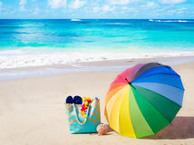 Summer background with rainbow umbrella. And bag on the sandy beach Royalty Free Stock Photo