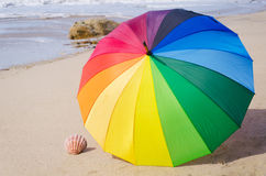 Summer background with rainbow umbrella. On the sandy beach Royalty Free Stock Photos