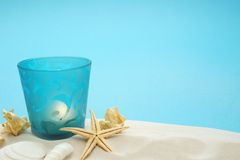 Summer background. With sand, starfish, seashells and candle Blue background with copy space Royalty Free Stock Images