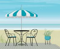 Summer background of Striped Teal Parasol and Bistro Table on Boardwalk Royalty Free Stock Photo