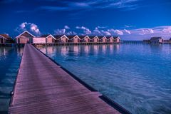 Sunset on Maldives island, luxury water villas resort and wooden pier. Beautiful sky and clouds and beach background Stock Image