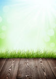 Summer background with wooden floor, green grass and bokeh Royalty Free Stock Image