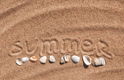 Summer background. Word summer and seashells on the sand Stock Image
