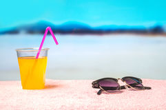 Summer background with yellow cocktail and sunglasses on towel on the beach. Beautiful blurred paradise ocean view. Stock Photo