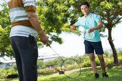 Summer badminton. Image of a cheerful guy playing badminton with his father in the park Stock Photography