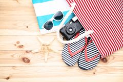 Bag with flip flops and camera. Summer bag with flip flops and retro camera on wooden table royalty free stock photo