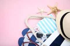 Summer bag with flip flops and starfishes. On pink background royalty free stock images