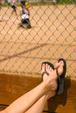 Summer at the ballpark. Spectator's feet propped up on a softball fence in the summertime watching the game Royalty Free Stock Photos