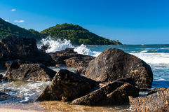 Summer in Balneario Camboriu. A summer scene in one beach of Balneario Camboriu, Southern Brazil. Rocks on the sea water and on the background green mountains Stock Photography
