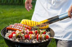 Summer Barbecue. Man with tongs cooking on a back yard barbecue Royalty Free Stock Photos