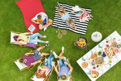 Summer barbecue party in backyard. Top view of group of young friends having summer barbecue party in the backyard with grill and table full of delicious food royalty free stock image