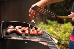 Summer Barbeque. Barbecuing hamburgers and hot dogs for a summer picnic Stock Image