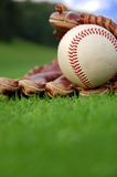 Summer baseball. Close up of a baseball glove on the grass Stock Image