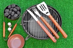 Summer BBQ Grill Party Or Picnic Concept. Barbecue Charcoal Kettle Grill With Tools, Charcoal Briquettes, Plate Are On The Bright Green Grass Background. Top Royalty Free Stock Photos