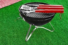 Summer BBQ Grill Party Or Picnic Concept. Barbecue Charcoal Kettle Grill With Tools, Picnic Red Tablecloth Are On The Bright Green Grass Background Royalty Free Stock Photo