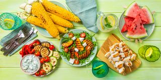Summer bbq party concept - grilled chicken, vegetables, corn, salad, top view. Copy space stock photo