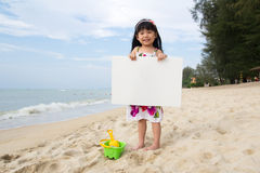 Summer beach. Little child girl holds a white board at beach Stock Image