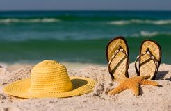 Summer at the Beach. A starfish, shell trimmed sandals and a yellow floppy hat set against the incoming ocean surf.  Shot with shallow DOF Royalty Free Stock Image