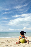 Summer beach. Asian baby girl with coconut fruit on beach Royalty Free Stock Photography