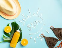 Summer beach accessories sunscreen hat bathing bottle orange juice blue background text SUN. The concept relaxation stock images