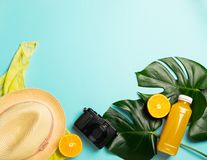 Summer beach accessories sunscreen hat scarf orange juice bottle bright blue background. The concept of relaxation and royalty free stock photo