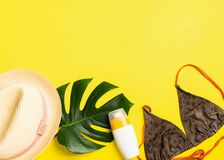 Summer beach accessories sunscreen summer hat swimsuit bright yellow background. Summer holiday concept and beach. royalty free stock images