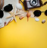 Summer Beach Accessories on Yellow Background. Camera, Starfish,. Sunglasses, Sea Shell, and Hat. Flat Lay Room For Text Royalty Free Stock Photo