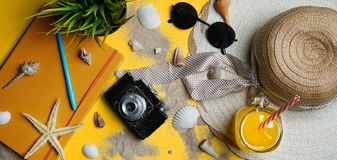 Summer Beach Accessories on Yellow Background. Camera, Starfish,. Sunglasses, Sea Shell, Orange Juice and Sun Hat. Flat Lay Banner Stock Photo