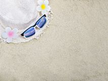 Straw hat and sunglasses on sand for summer beach background. stock image