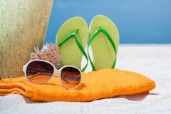 Summer beach bag with coral,towel,sunglasses and flip flops. On sandy beach Royalty Free Stock Photos