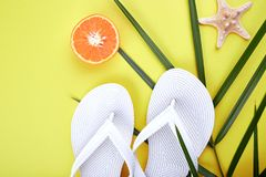 Summer beach bag with flip flops,. Summer beach bag with white flip flops, seashells, orange fruit on yellow background. Flat lay. Top view. Copy space Royalty Free Stock Photos