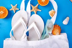Summer beach bag with flip flops,. Summer beach bag with white flip flops, sunglasses, seashells, orange fruit on blue background. Flat lay. Top view. Copy space Royalty Free Stock Images