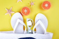 Summer beach bag with flip flops,. Summer beach bag with white flip flops, sunglasses,  seashells, orange fruit on yellow background. Flat lay. Top view. Copy Stock Image