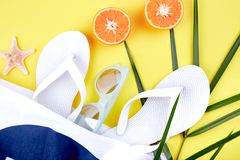 Summer beach bag with flip flops,. Summer beach bag with white flip flops, sunglasses,  seashells, orange fruit on yellow background. Flat lay. Top view. Copy Royalty Free Stock Photo