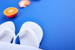 Summer beach bag with flip flops,. Summer beach bag with white flip flops, seashells, orange fruit on blue background. Flat lay. Top view. Copy space Stock Photography