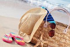 Summer beach bag on sandy beach. Closeup of summer beach bag with items on sandy beach Stock Photography